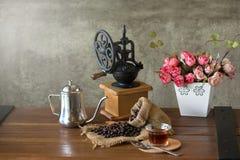 Amoladora de café manual del vintage con los granos y la taza de café Foto de archivo