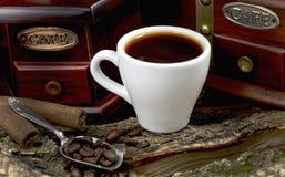Amoladora de café manual del vintage con los granos y la taza de café Imagen de archivo libre de regalías