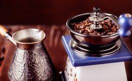Amoladora de café mecánica, viejo cezve de cobre y granos de café Sobre la tabla de madera como fondo Imagen de archivo