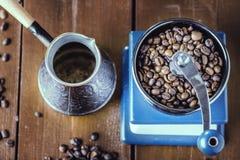 Amoladora de café mecánica, viejo cezve de cobre y granos de café Sobre la tabla de madera como fondo Fotos de archivo