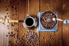 Amoladora de café mecánica, viejo cezve de cobre y granos de café Sobre la tabla de madera como fondo Fotografía de archivo libre de regalías