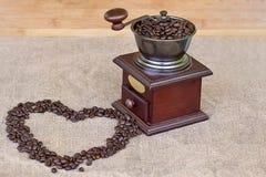 Amoladora de café por completo de la forma asada del corazón de los granos de café y de los granos de café Imagenes de archivo