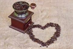 Amoladora de café por completo de la forma asada del corazón de los granos de café y de los granos de café Imagen de archivo