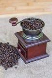 Amoladora de café por completo de los granos de café y de las gotas asados del café en el lado derecho - del top Imagenes de archivo