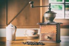 Amoladora de café vieja en un cortijo rústico con los granos de café, el jarro de leche y la taza de café imagen de archivo