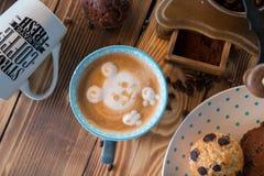 Amoladora de café y taza de café viejas con los granos y las galletas dispersados de café en fondo de madera Imagenes de archivo