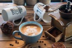 Amoladora de café y taza de café viejas con los granos y las galletas dispersados de café en fondo de madera Imágenes de archivo libres de regalías
