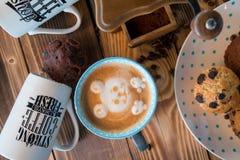 Amoladora de café y taza de café viejas con los granos y las galletas dispersados de café en fondo de madera Imagen de archivo