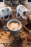 Amoladora de café y taza de café viejas con los granos y las galletas dispersados de café en fondo de madera Fotos de archivo libres de regalías