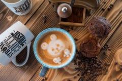 Amoladora de café y taza de café viejas con los granos y las galletas dispersados de café en fondo de madera Foto de archivo libre de regalías