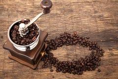 Amoladora del grano de café del vintage al lado de los granos de café de la forma del círculo fotografía de archivo libre de regalías