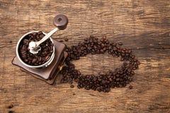 Amoladora del grano de café del vintage al lado de los granos de café de la forma del círculo imagen de archivo