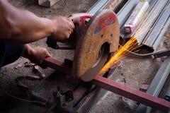 Amoladora del uso del trabajador para cortar el tubo Imagenes de archivo