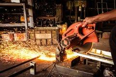 Amoladora eléctrica que corta el acero Trabajador con la herramienta eléctrica de la amoladora en fábrica con las chispas del fue fotografía de archivo