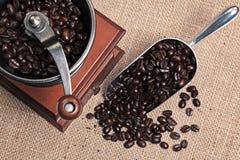 Amoladora y cucharada de café por completo de habas Foto de archivo libre de regalías