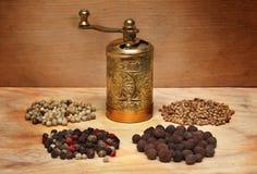 Amoladora y especias en un tablero de madera Foto de archivo libre de regalías