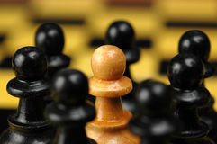 Amongst the others. White pawn on a chess board surrounded by black ones Stock Images