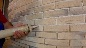 Amontonamiento de la piedra decorativa en la pared, restauración de juntas entre las placas