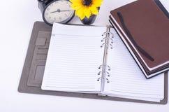 Amontonamiento de los diarios, del reloj del vintage y de la planta artificial en la tabla blanca Imagen de archivo