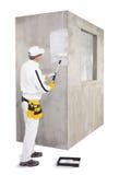 Amorçage de travailleur avec un mur de ciment de rouleau de peinture Photographie stock