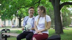 Amorös tonåring som hoppar över bänk och framlägger blommor till flickvännen, datum arkivfilmer