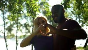 Amorösa par för blandat lopp som visar hjärtaform med händer, mellan skilda raser förbindelse royaltyfri foto