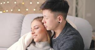 Amor, abrazo joven de los pares en el sofá en hogar metrajes