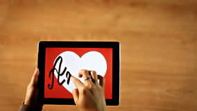 Amor calligraphy. Female writing inside white heart on tablet stock footage
