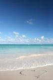 Amor: Corazón en la playa de la arena, océano tropical Fotos de archivo libres de regalías