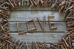 Amor da inscrição com as varas de madeira no fundo de madeira Fotografia de Stock Royalty Free