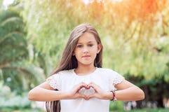 Amor da mão Menina bonita que mostra um símbolo do coração no parque Foto de Stock Royalty Free