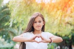 Amor da mão Menina bonita que mostra um símbolo do coração no parque Imagem de Stock Royalty Free