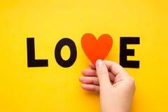 AMOR da palavra com mão na superfície amarela simples do fundo Foto de Stock Royalty Free