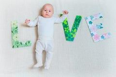 Amor da palavra com pés do bebê Fotografia de Stock Royalty Free