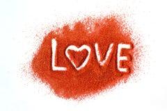 AMOR da palavra escrito à mão no açúcar vermelho no fundo branco Desejos para o dia de Valentim Declaração do amor fotos de stock royalty free