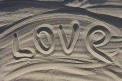 Amor da palavra tirado na areia na luz solar do por do sol como o fundo do amor fotos de stock royalty free