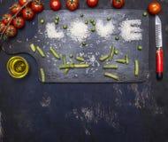 Amor de la inscripción, arroz presentado en una tabla de cortar con la frontera de la pimienta, de la pasta de tomate y de la man foto de archivo