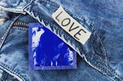 AMOR de la inscripción en el papel y el condón rasgados en paquete azul de la hoja en vaqueros Fotos de archivo