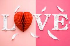 Amor de la inscripción de la foto hecho de hojas y de flores en fondo rosado Imagen de archivo libre de regalías