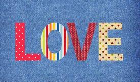 Amor de la letra de la materia textil sobre vaqueros Fotografía de archivo libre de regalías