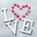 Amor de la palabra del texto del día de fiesta del día de tarjetas del día de San Valentín con el corazón rosado del merengue Imagen de archivo