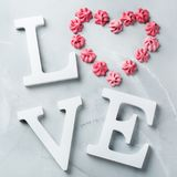 Amor de la palabra del texto del día de fiesta del día de tarjetas del día de San Valentín con el corazón rosado del merengue Foto de archivo libre de regalías