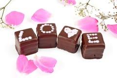 AMOR de la palabra deletreado en las almendras garapiñadas del chocolate Fotografía de archivo