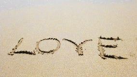 Amor de la palabra en la arena que limpió apagado almacen de video