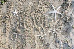 Amor de la palabra en la arena Imágenes de archivo libres de regalías