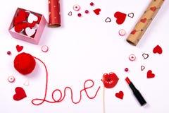 Amor de la palabra escrito con el hilo rojo de las lanas y los accesorios lindos foto de archivo