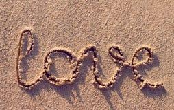 Amor de la palabra manuscrito en una playa tropical Fotos de archivo libres de regalías
