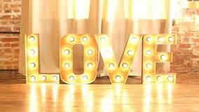 Amor de la palabra que brilla intensamente con las bombillas almacen de video