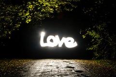 Amor de la palabra que brilla intensamente en el Freezelight oscuro Foto de archivo
