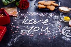 Amor de las letras de la crema del merengue de la visión superior usted en el fondo de piedra negro con los ingredientes, la flor Fotografía de archivo